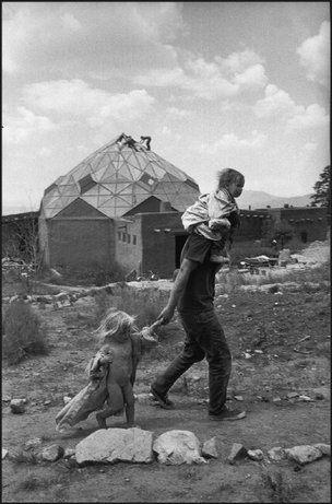 NEW MEXICO—At the Lama Foundation community, a father and two children pass in front of the kitchen, a stoutly built octagonal wood and glass structure (geodesic dome) with all the things a kitchen should have, plus a dining room above, 1971. © Henri Cartier-Bresson / Magnum Photos