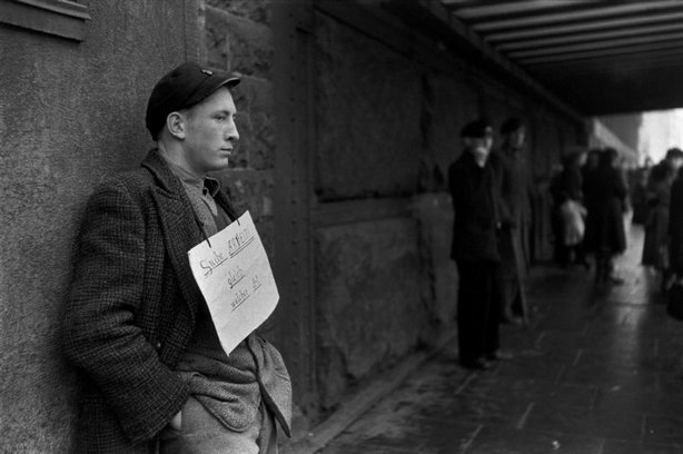 "HAMBURG, West Germany—Around the neck of a young man hangs a sign that reads, ""I am looking for any kind of work,"" December 1952-January 1953. © Henri Cartier-Bresson / Magnum Photos"