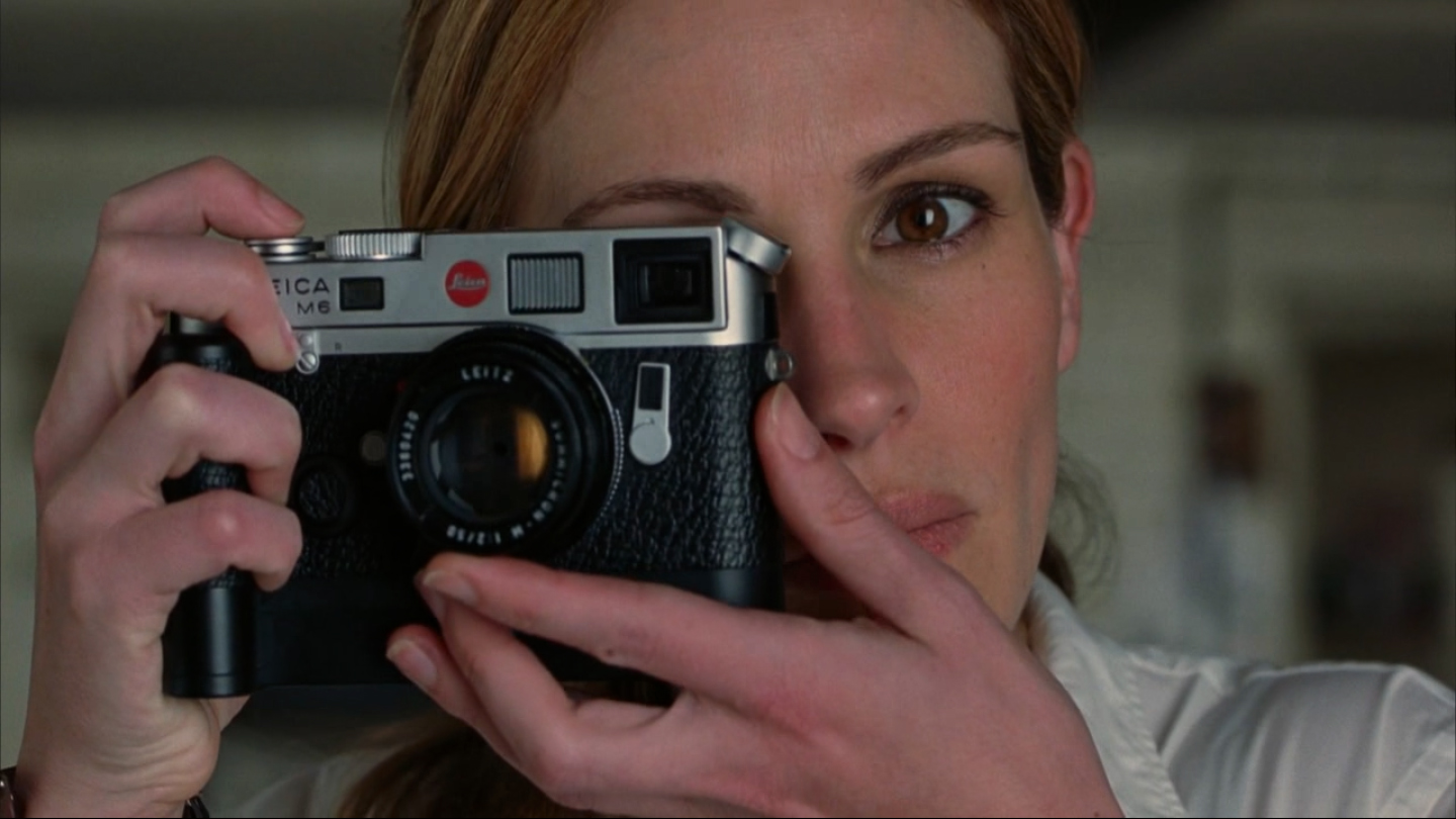 Julia Roberts shooting Natalie Portman with a chrome Leica M6 TTL and 50mm Summicron; from the movie Closer (2004)