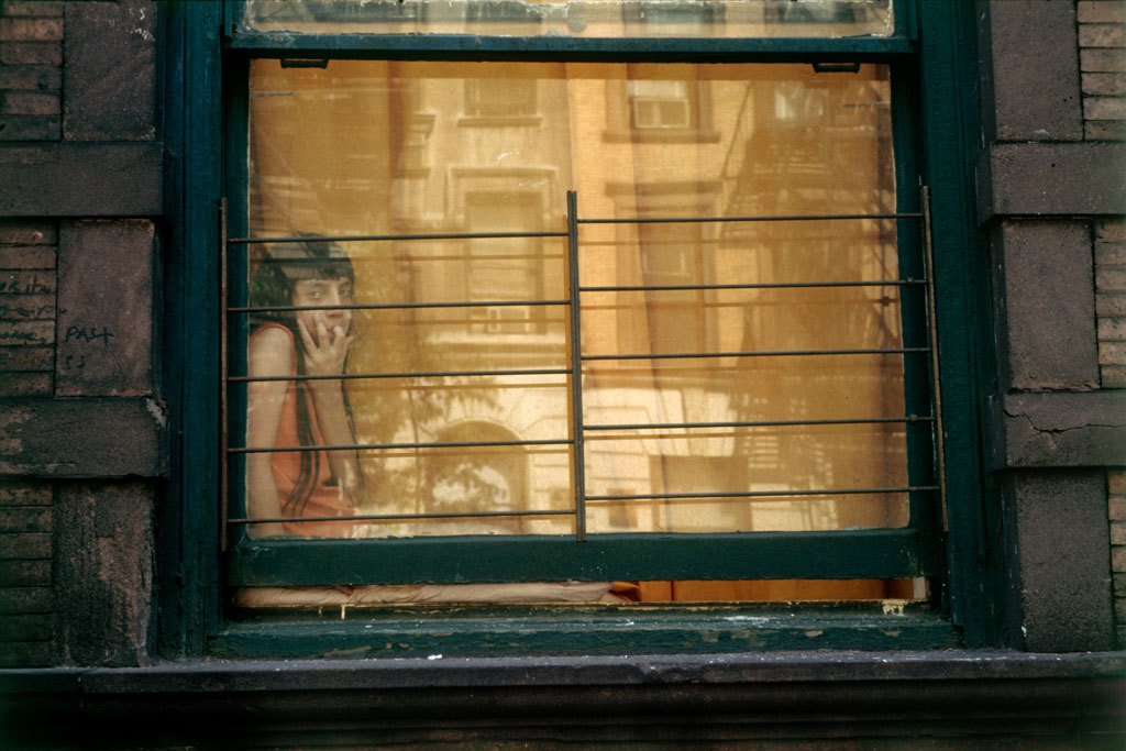 Girl in window, orange reflection, New York, 1972 © Helen Levitt