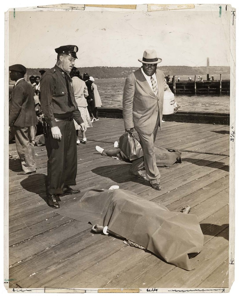 Police officer and lodge member looking at blanket-covered body of woman trampled to death in excursion-ship stampede, New York, August 18, 1941 © Weegee