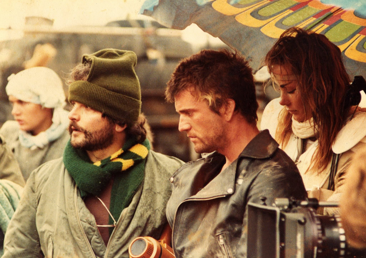 George Miller, Mel Gibson & Virginia Hey on the set of Road Warrior (1981).